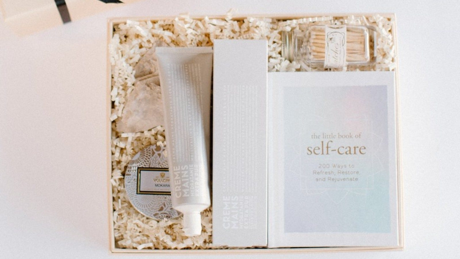 a light colored gift box with a self care book, a tube of hand cream, matches, and a candle