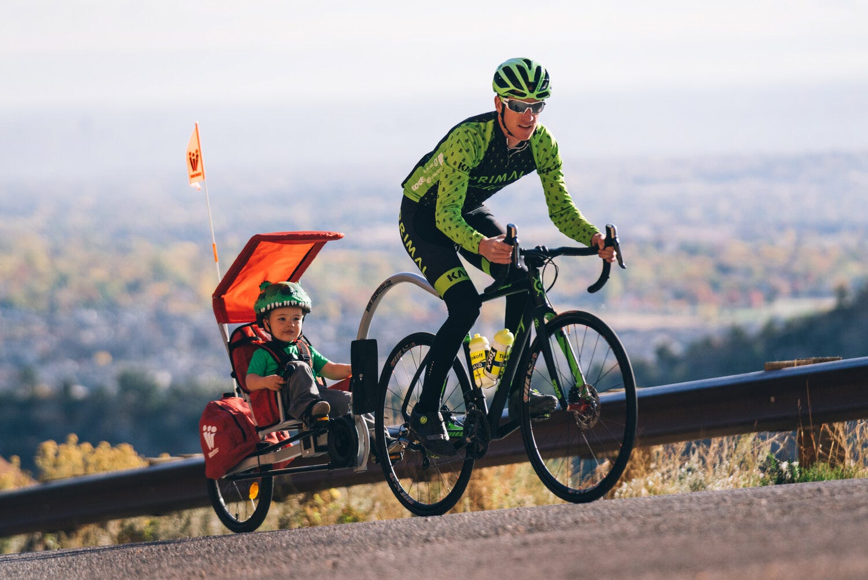 أخرج الأب ابنه للعب ، راكبًا مقطورة دراجة أطفال مضحكة تحمل علامة Weehoo.