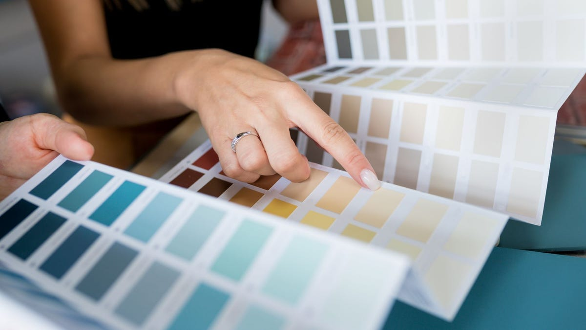 A woman choosing a wall paint color from samples.