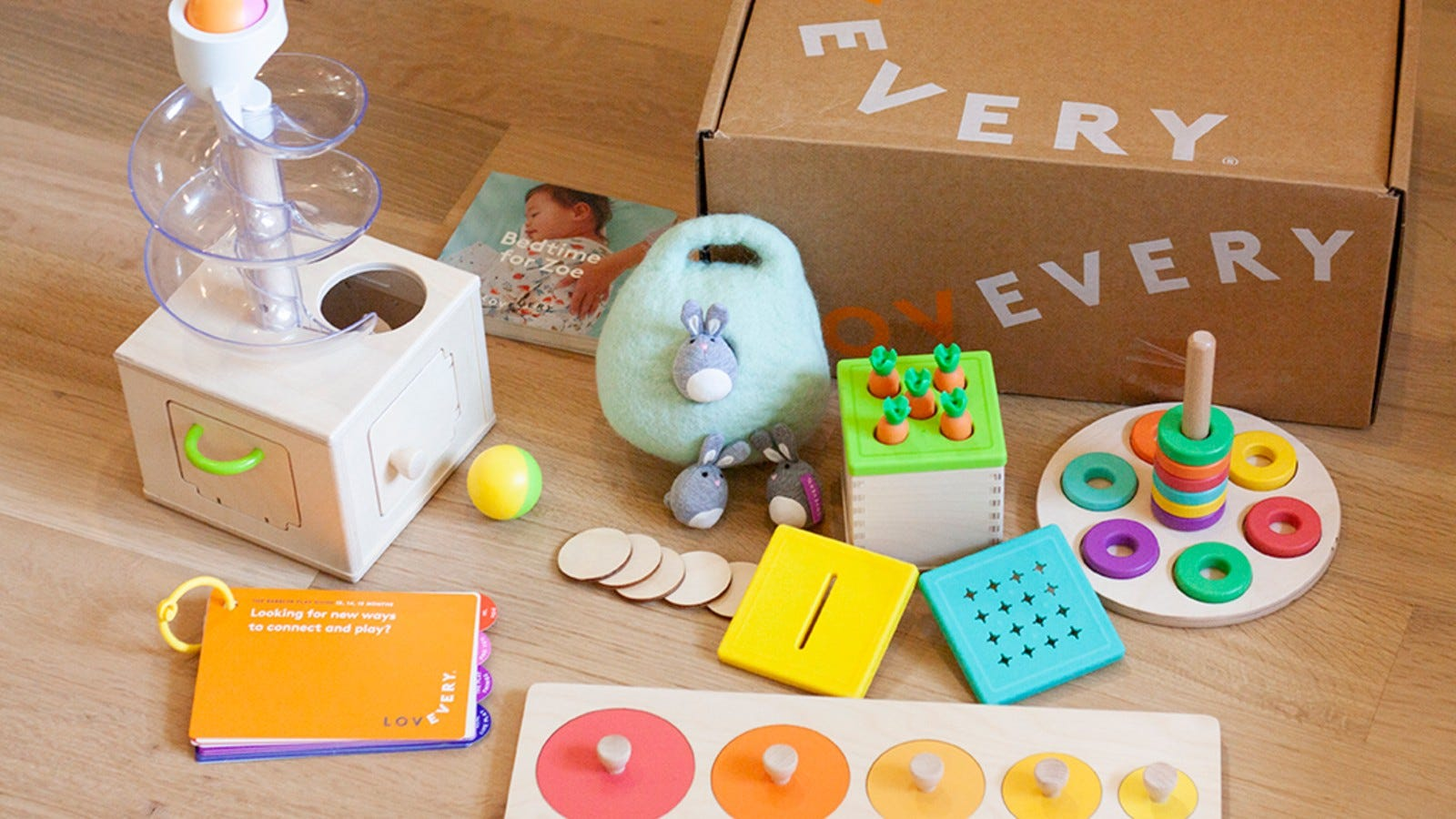 a cardboard box surrounded by colorful wooden toys for a baby