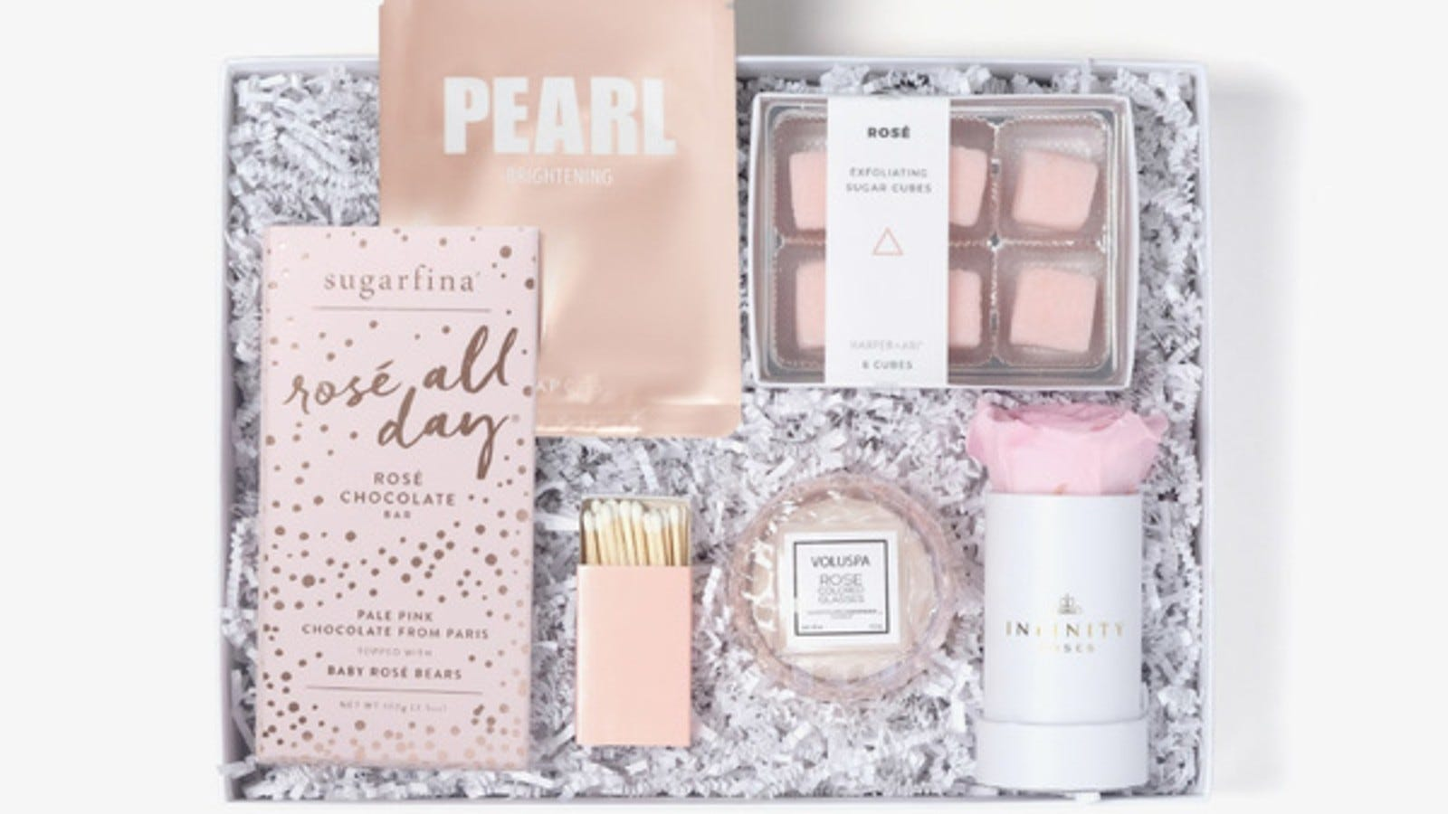 pink and white gift box that includes a sheet mask, exfoliating cubes, a candle, chocolate bar, and a pink rose