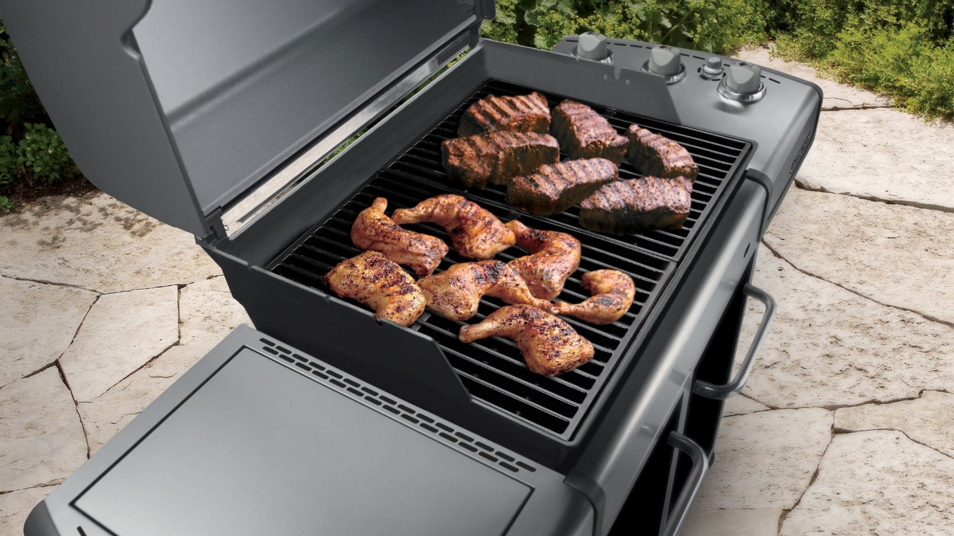 Various meats roasting on Weber grill grates.