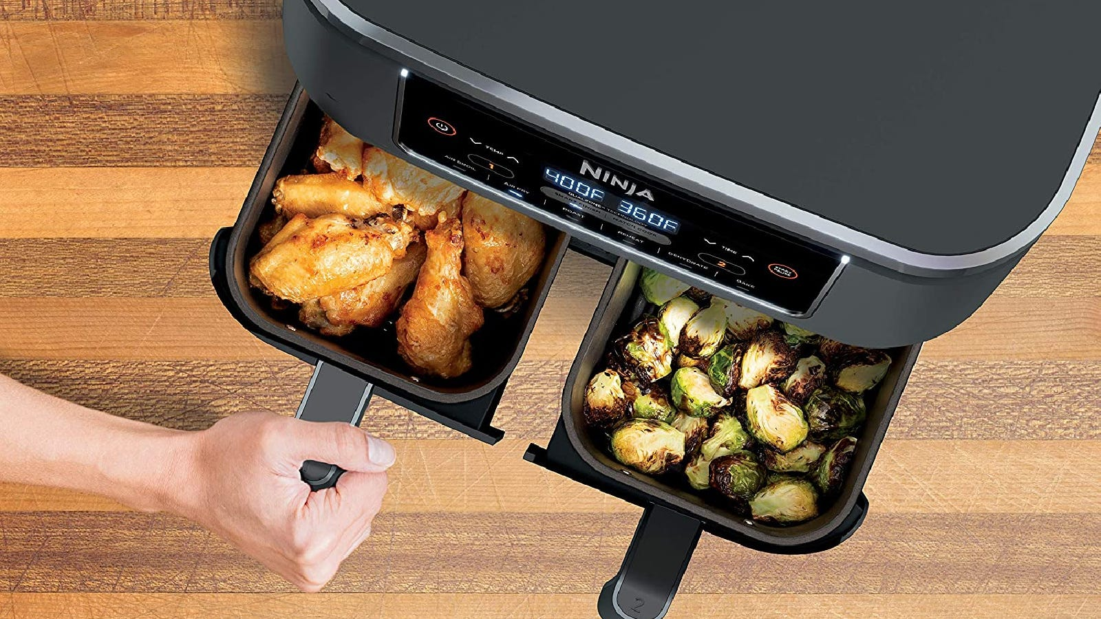 Someone opening a compartment to the Ninja Foodi two-basket air fryer filled with chicken wings on one side and perfectly crispy brussels sprouts on the other side.