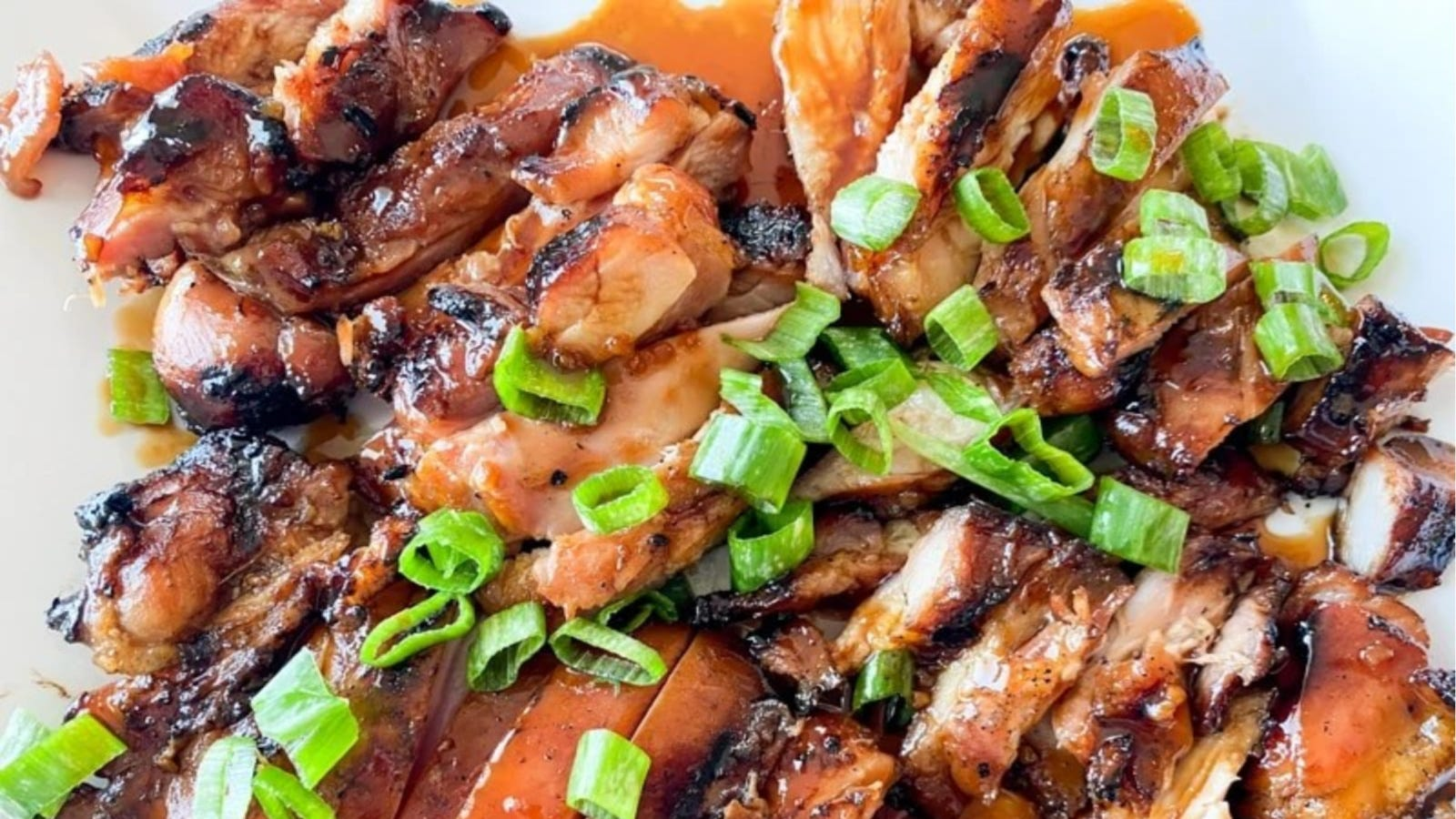 A plate of grilled Hawaiian teriyaki chicken topped with chopped green onions.