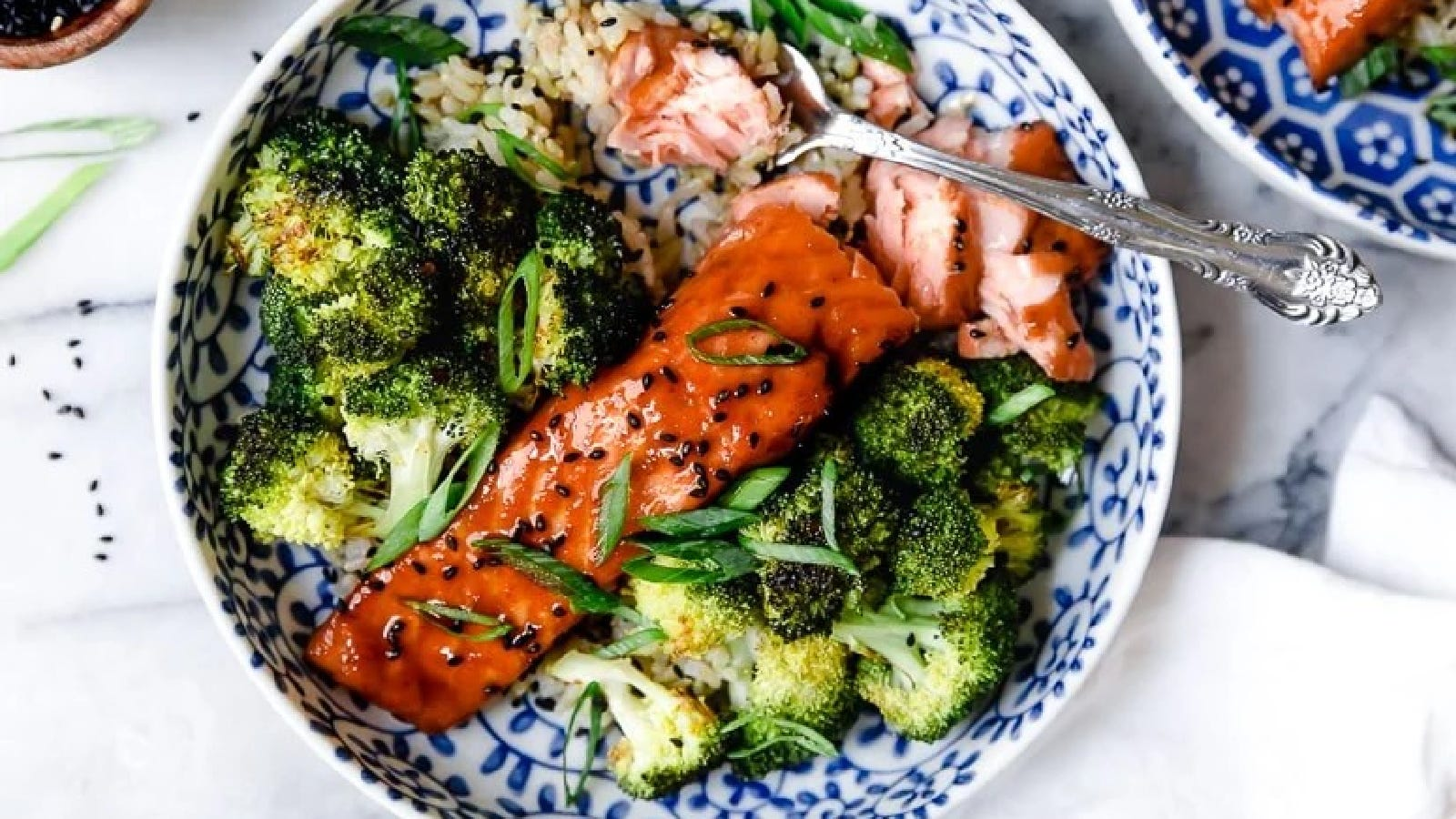 Maple soy air-fried salmon on a plate topped with sesame seeds, with a side of brown rice and broccoli.