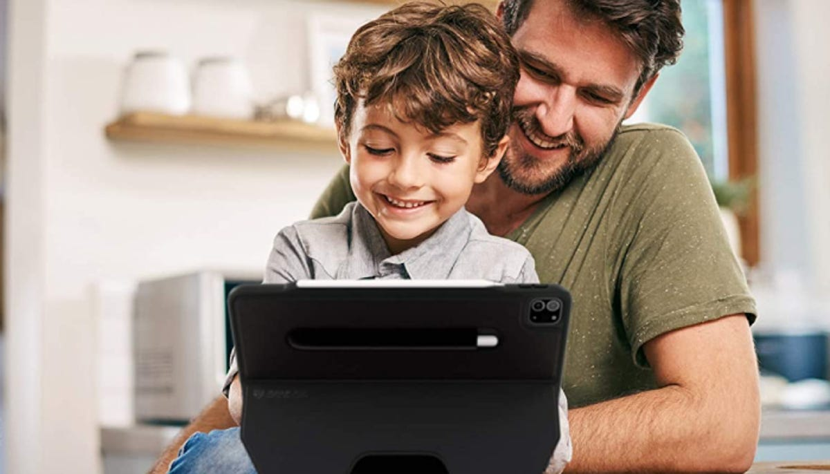 a young boy and his father looking at the screen of an iPad with a sturdy black case on it supporting it