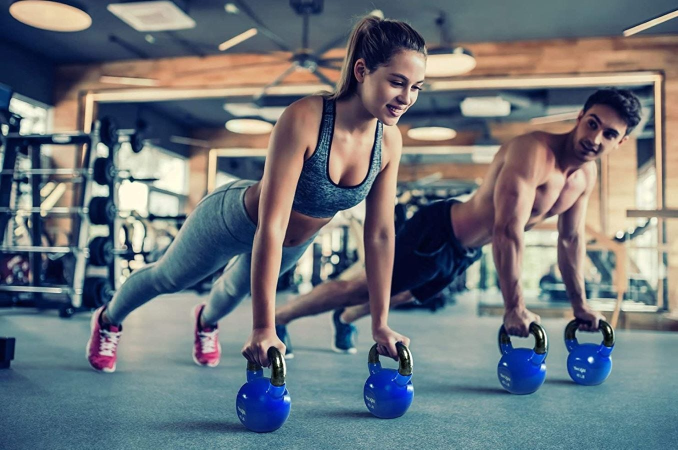 A man and woman using Yes4All kettlebells in a gym.
