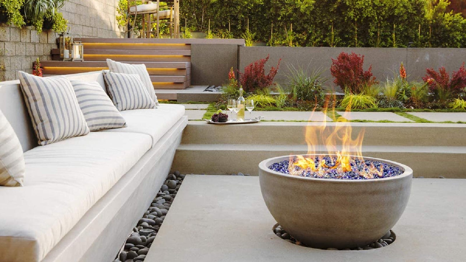 A bowl style fire pit filled with bright blue glass beads made by OnlyFire, on a beautiful dzen patio surrounded by lovely plants.