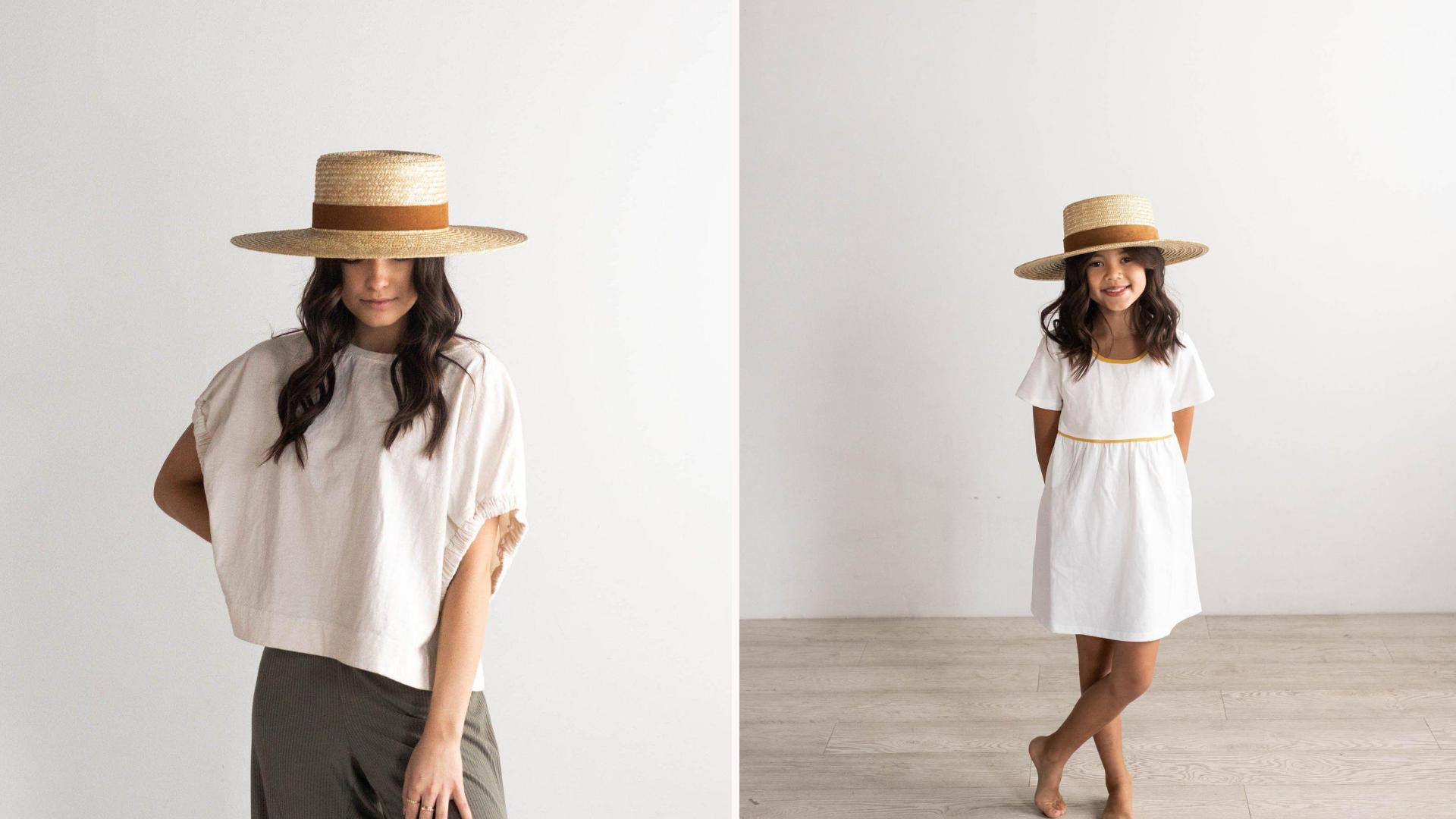 mom wearing a straw wide brim hat next to a child wearing a matching straw wide brim hat