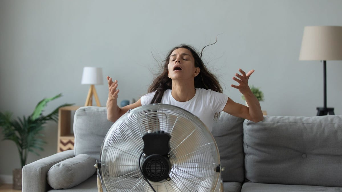 A woman sitting in front of a fan to cool off in summer heat.