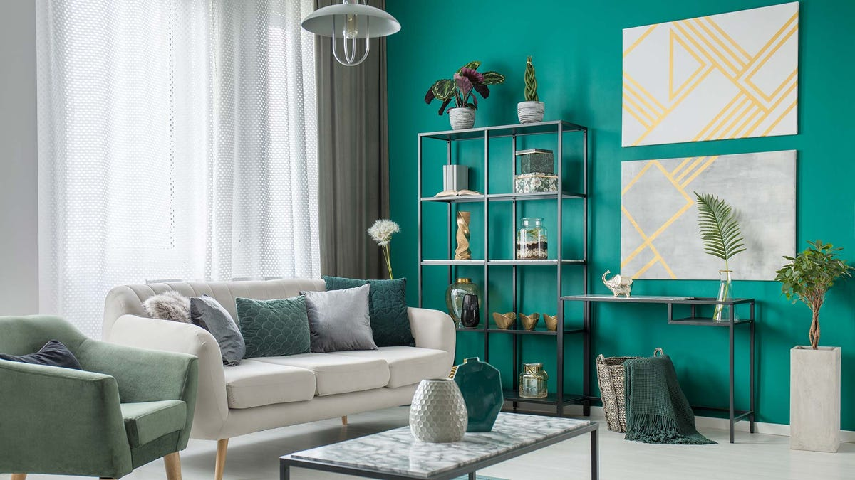 A living room with a bright turquoise colored wall and stylish furnishings.