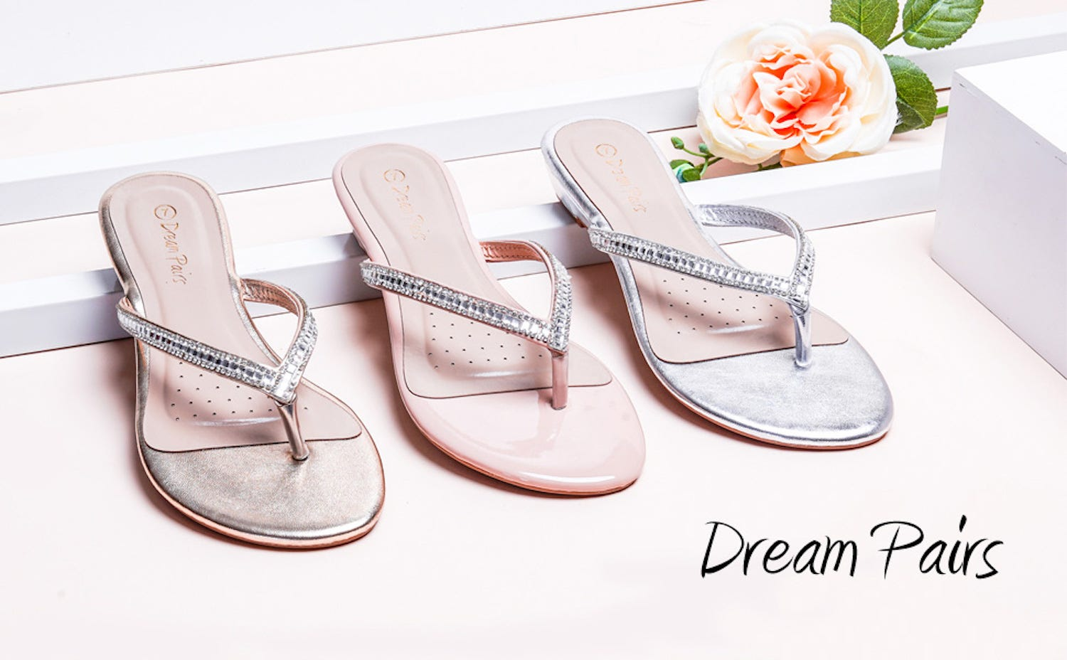 Three sparkly sandals, in bronze, pink, and silver, sitting on a white display