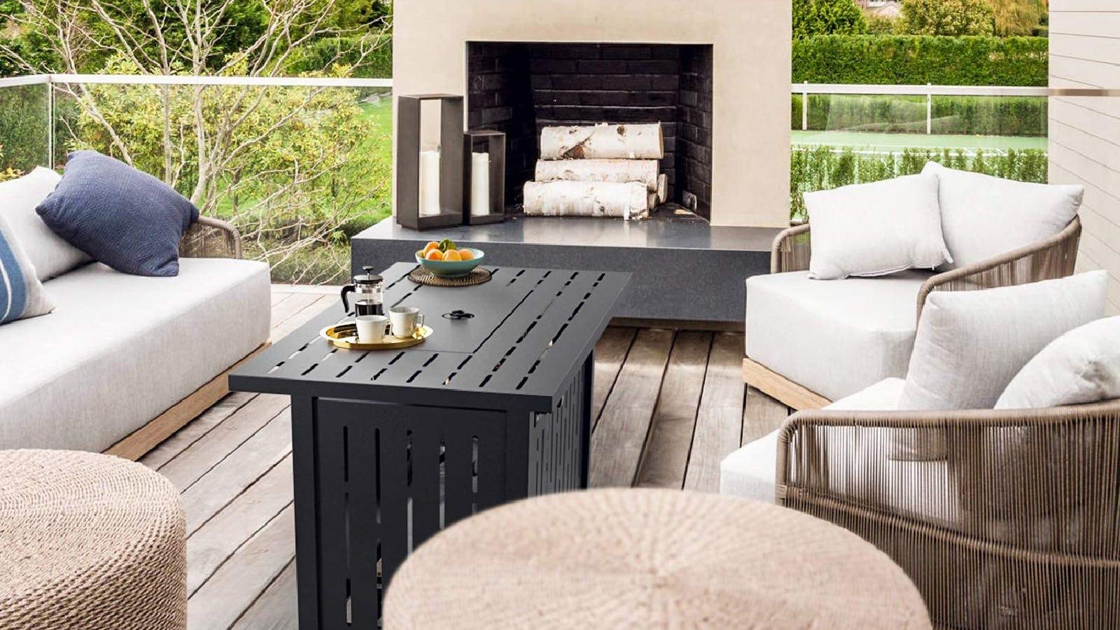 Uma mesa retangular SNAN colocada no meio de uma adorável mobília de jardim esbranquiçada ao ar livre, com algumas xícaras de café e uma cafeteira francesa.