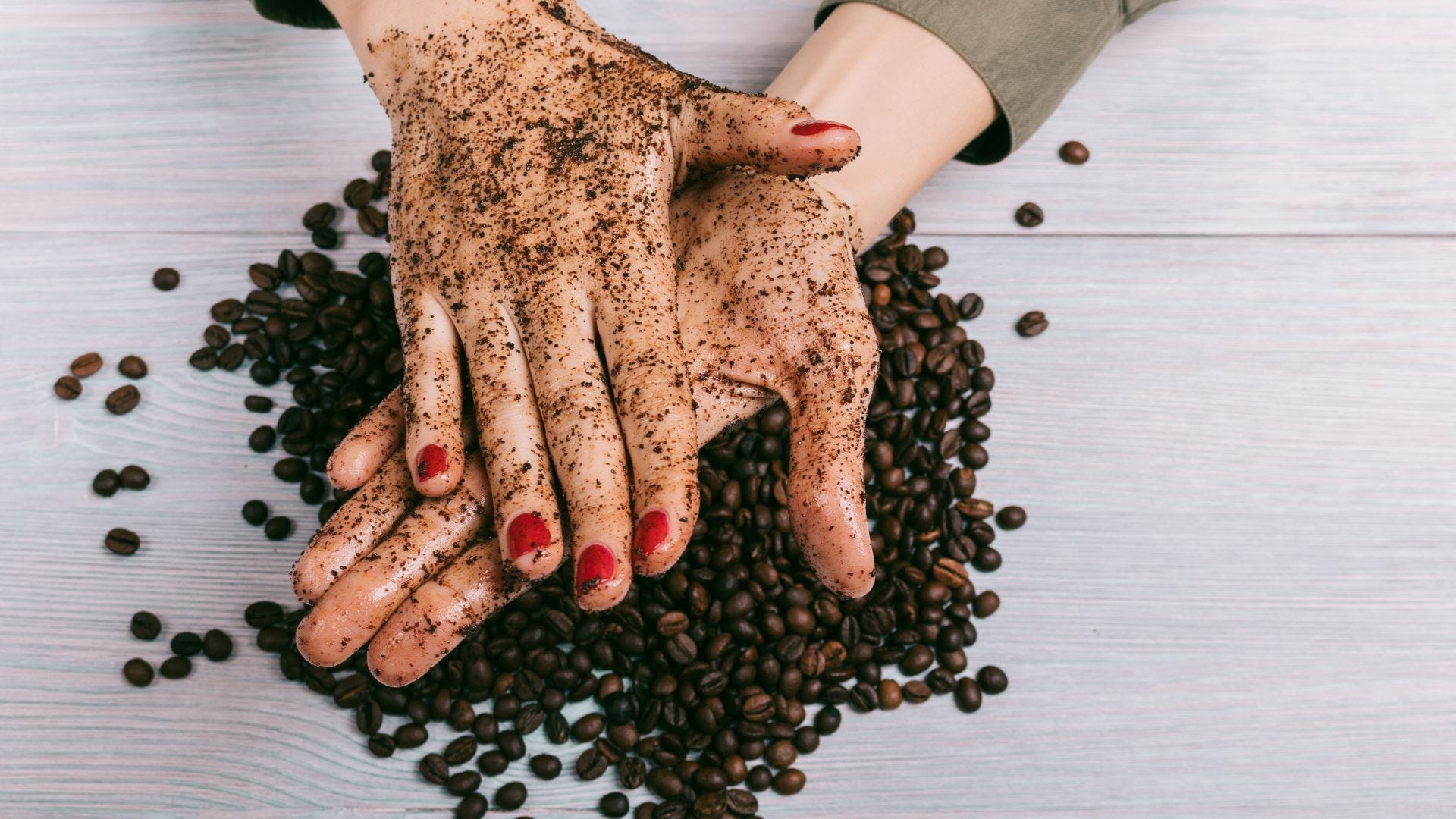A woman exfoliating her hands with coffee grounds.
