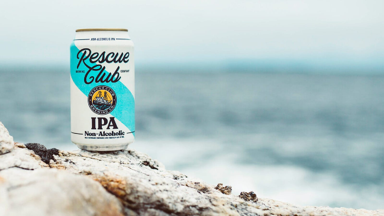 A can of Rescue Club Brewing IPA sitting along the rocks of a beach.