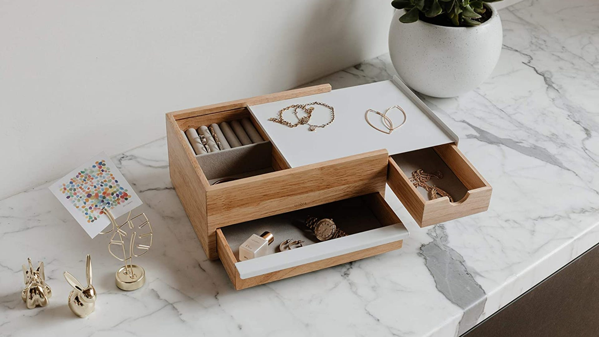 A top view of a wooden jewelry box with white accents holding gold jewelry.