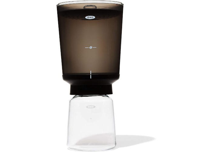 Two-tiered compact cold brew concentrate maker with a clear glass carafe on the bottom and plastic brewing compartment on top.