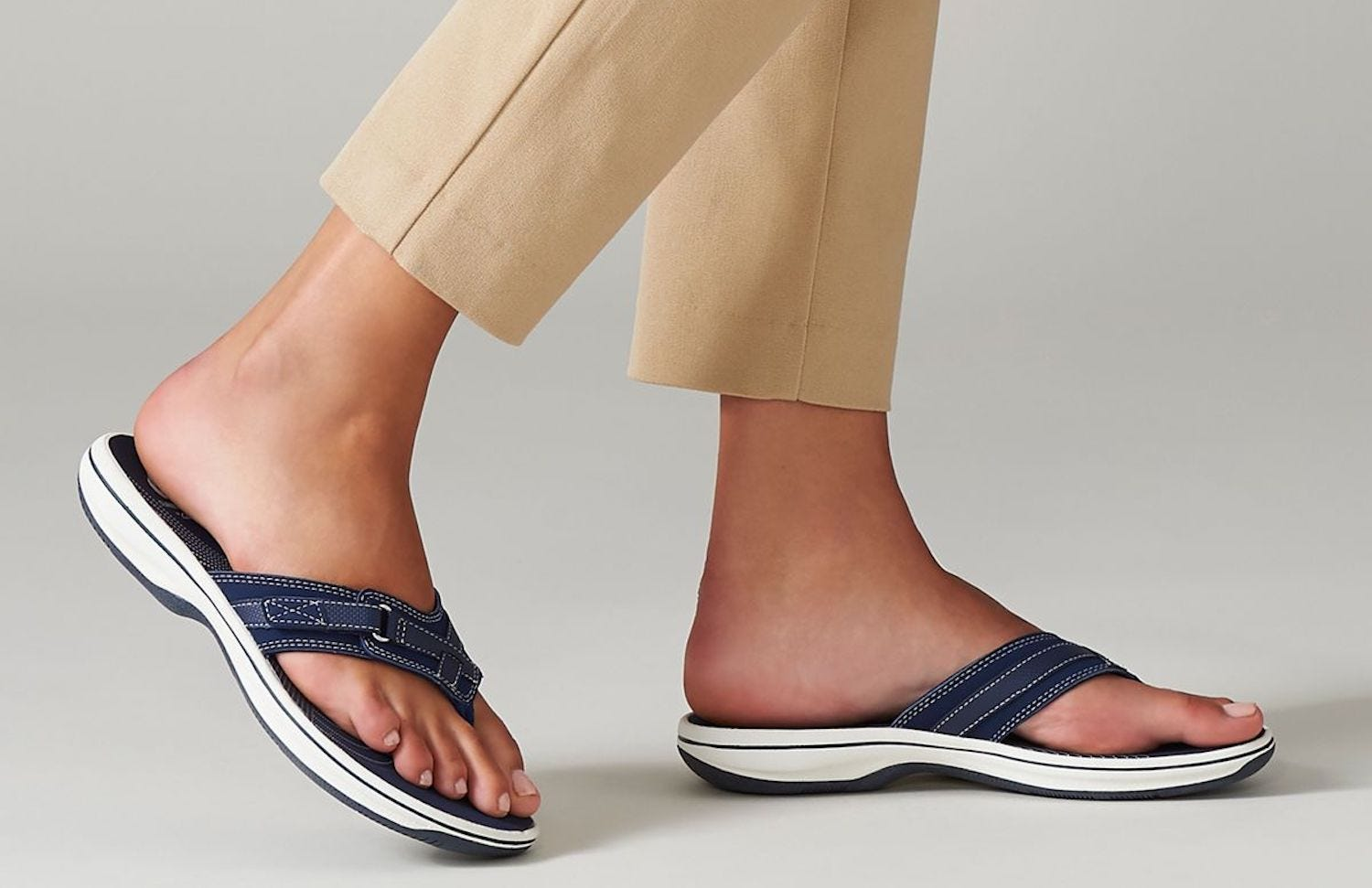 A woman's feet in cropped khaki pants and navy blue sandals