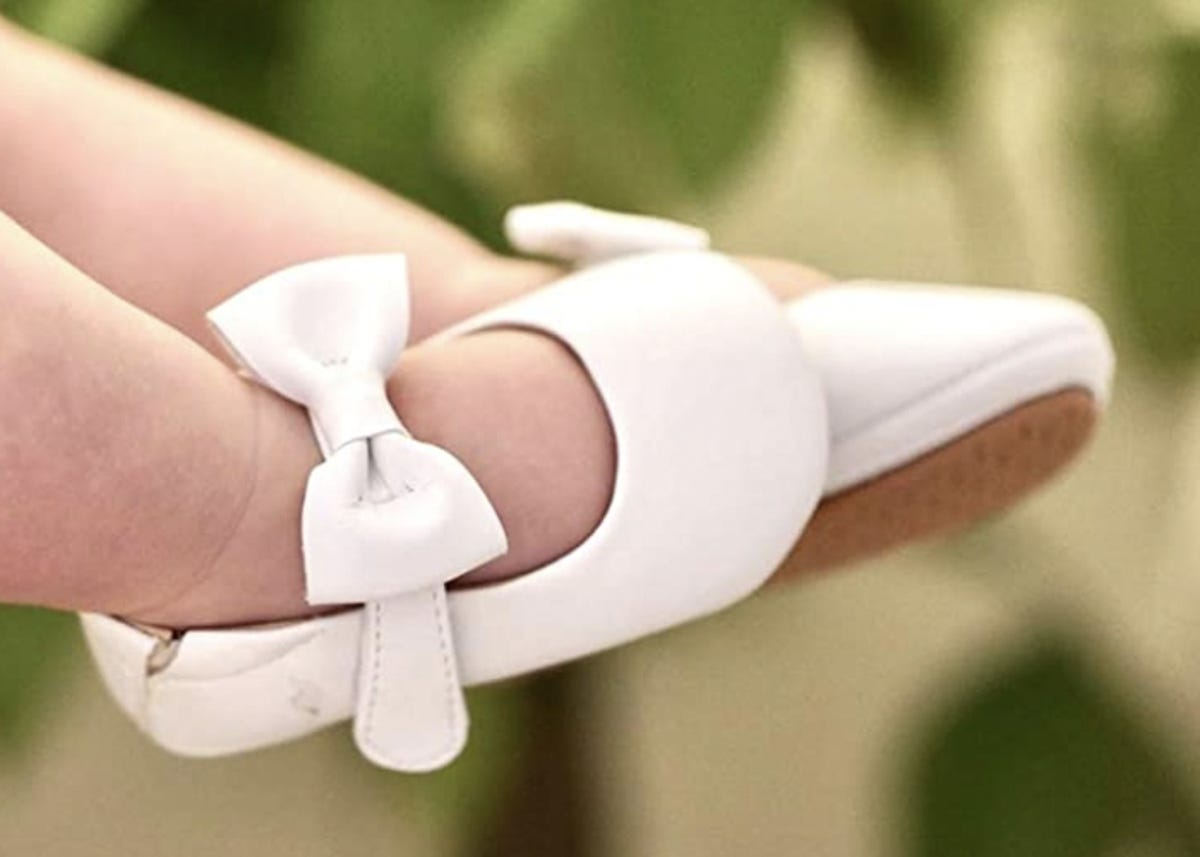 baby feet in white baby shoes with a bow on the strap across the top of the foot