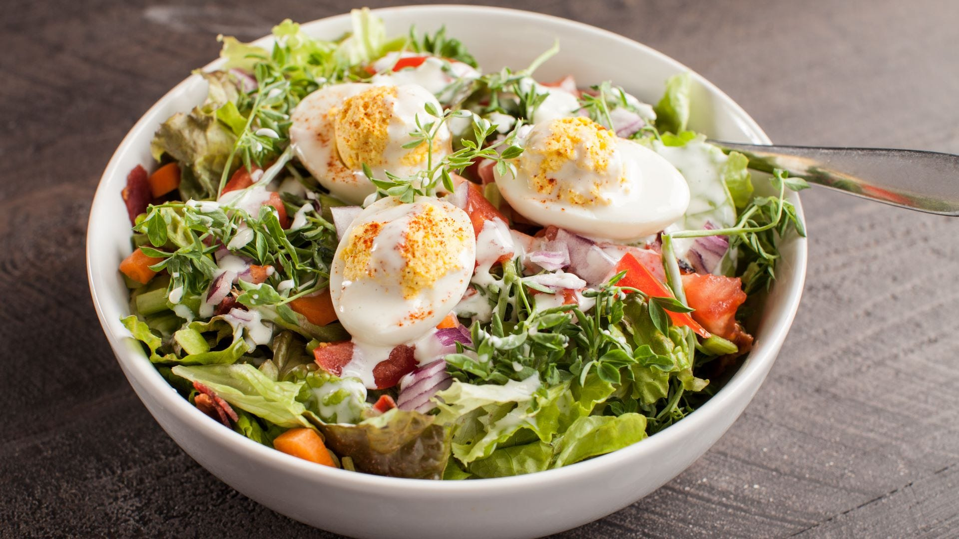 A bowl of salad with bacon and three deviled eggs on top.