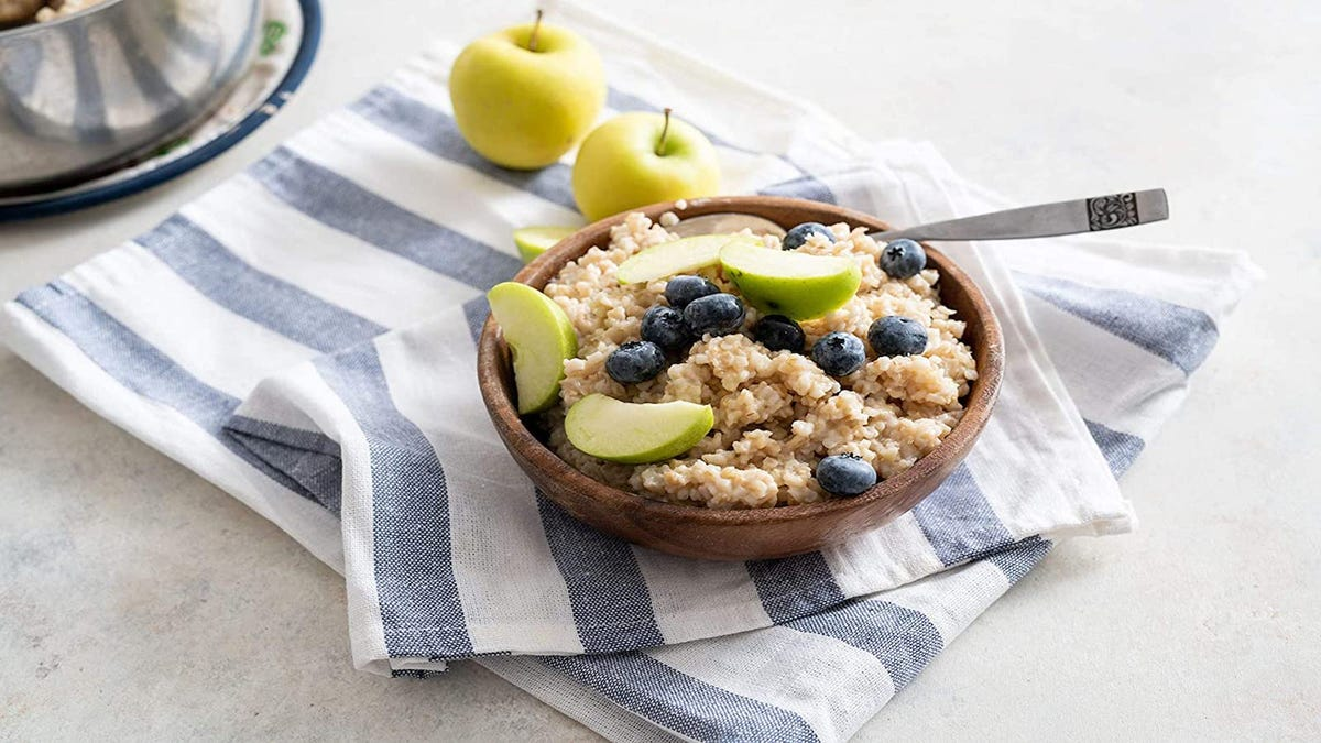 bowl of oatmeal with apples and blueberries on top; bowl is resting on a kitchen towel