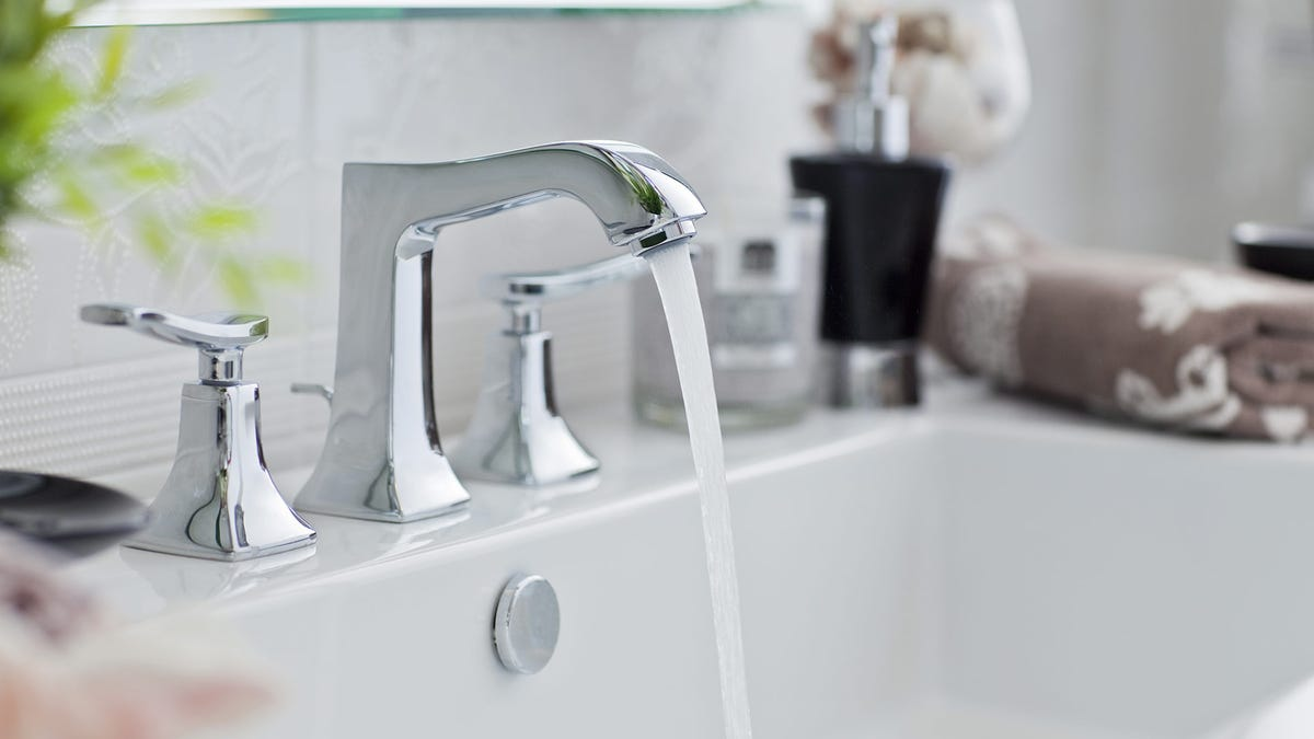 Water pours from a sparkling clean bathroom faucet into a polished white sink.