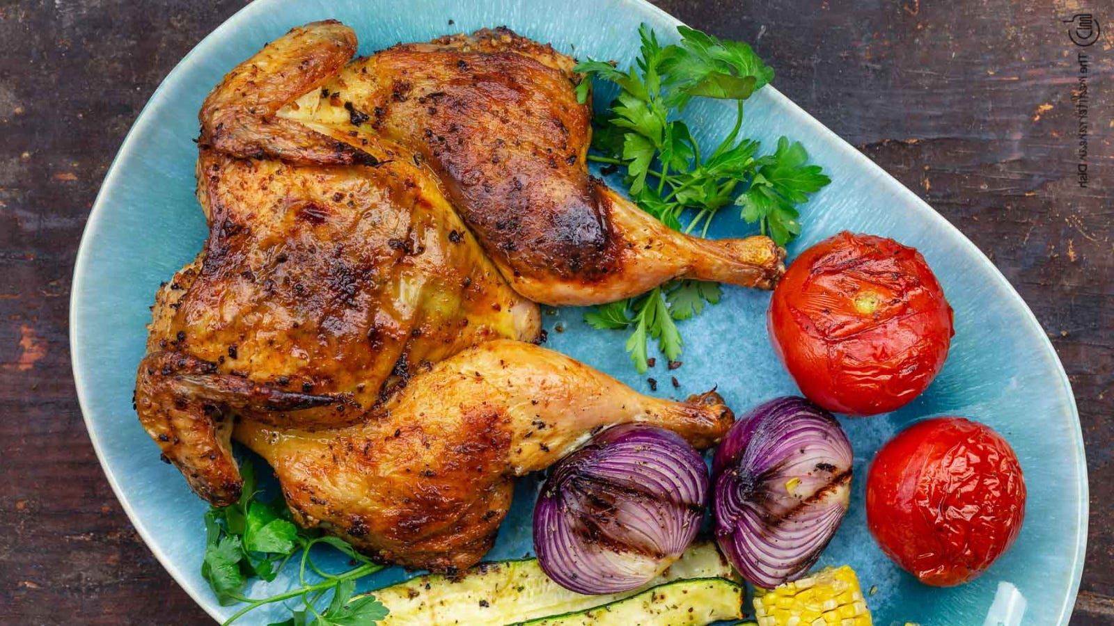A whole grilled chicken with grilled tomatoes, red onion and zucchini.