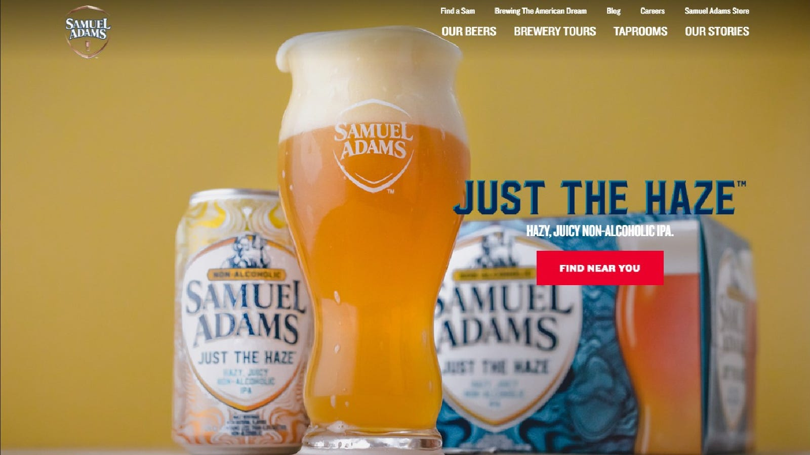 Samuel Adams Just the Haze non-alcoholic IPA freshly poured into a pint glass, with a 1 inch foam head, ready to be enjoyed, with a can and 6-pack box in the background.