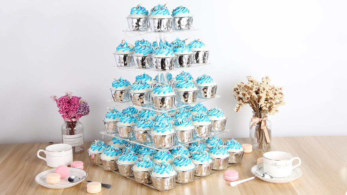 multiple blue frosted cupcakes on a clear acrylic cupcake stand, resting on top of a wooden table next to flowers, teacups, and macaron cookies