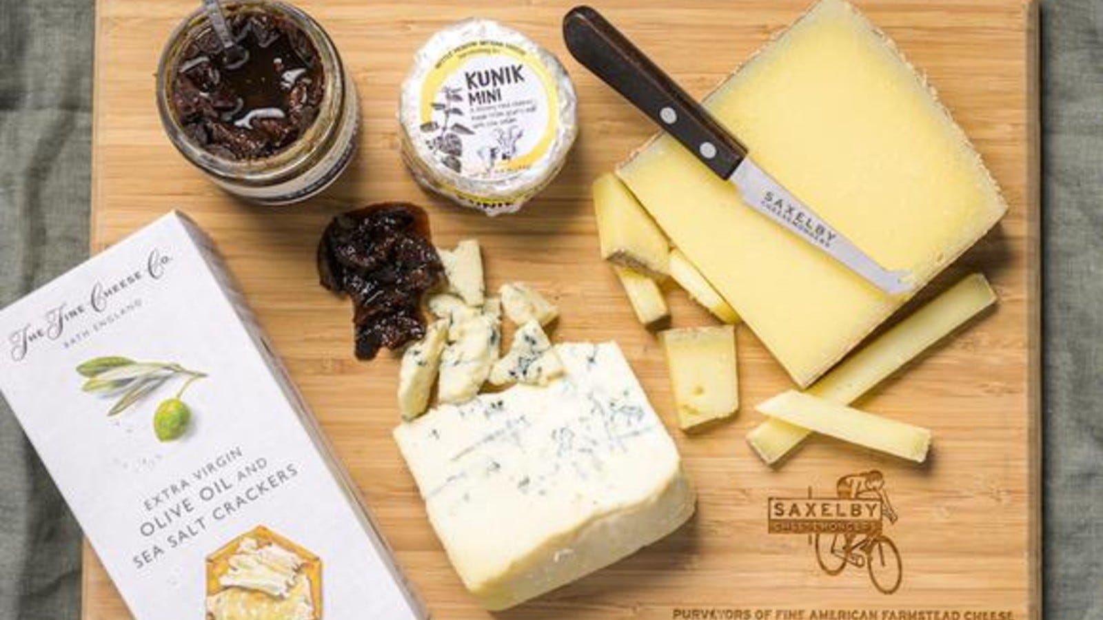 wooden cheeseboard with an assortment of cheese, jam, and crackers