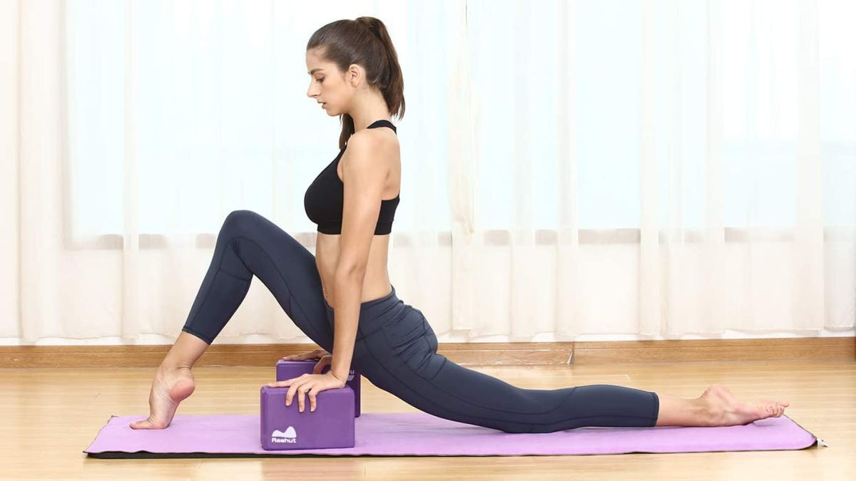 A woman doing a yoga pose while holding two purple yoga blocks.