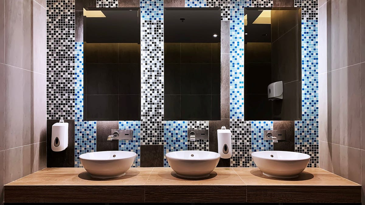 Three modern sinks in a public restroom.