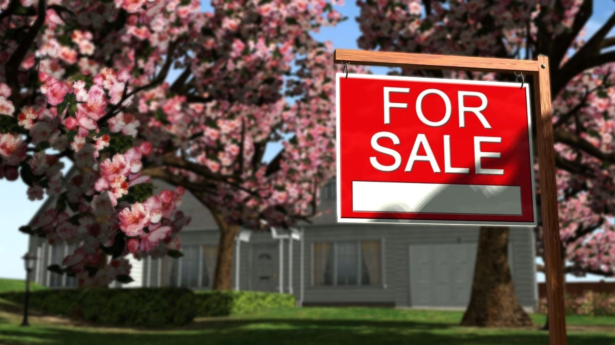 """A """"For Sale"""" sign in the front yard of a large home."""
