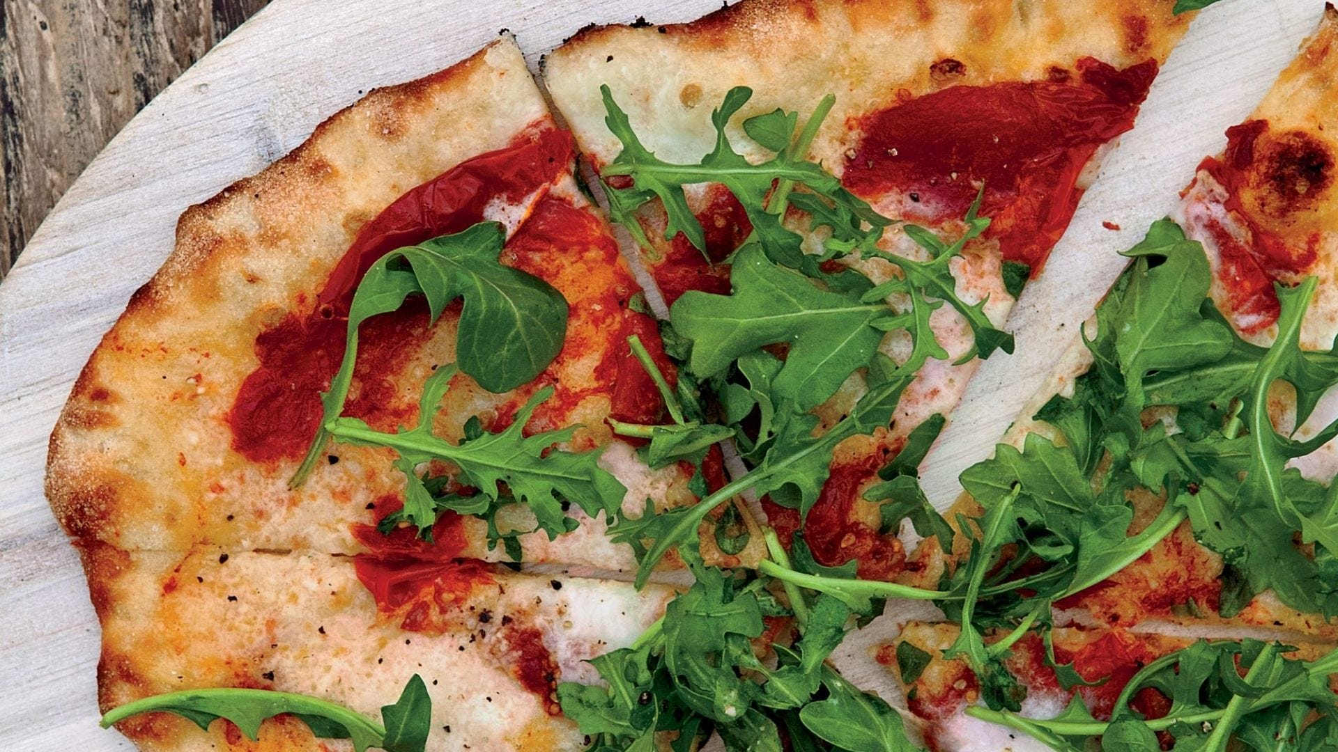 A pizza with tomato sauce and arugula.