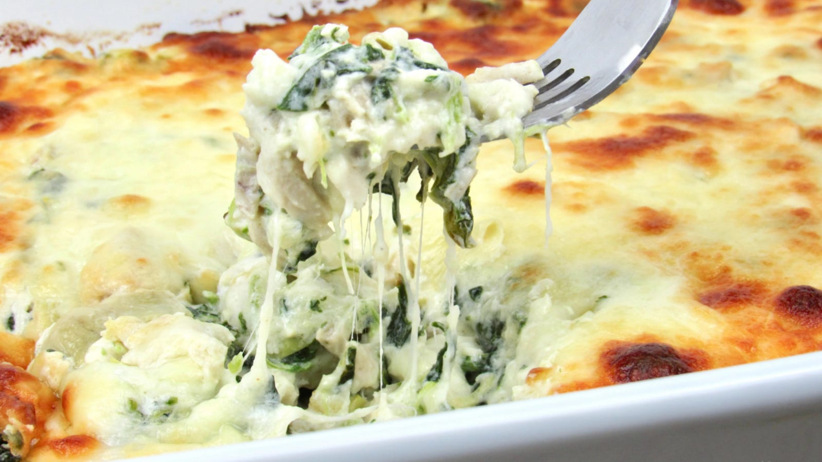 A bubbly hot casserole filled with chicken, spinach, artichoke and loads of melty cheese, with a bite sized piece being pulled up by a fork.