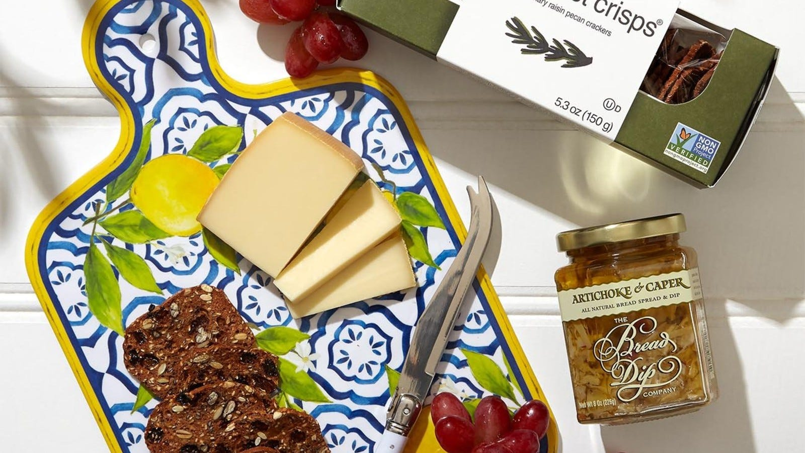 cheeseboard with crackers and cheese and grapes, a box of crackers, a jar of artichoke dip