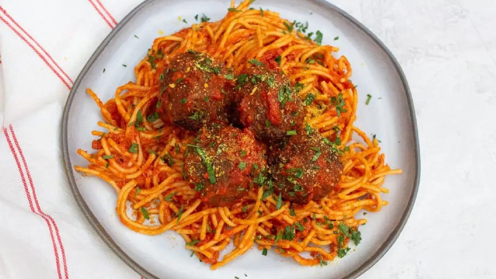 A plate of spaghetti tossed in red sauce topped with air fried meatballs.