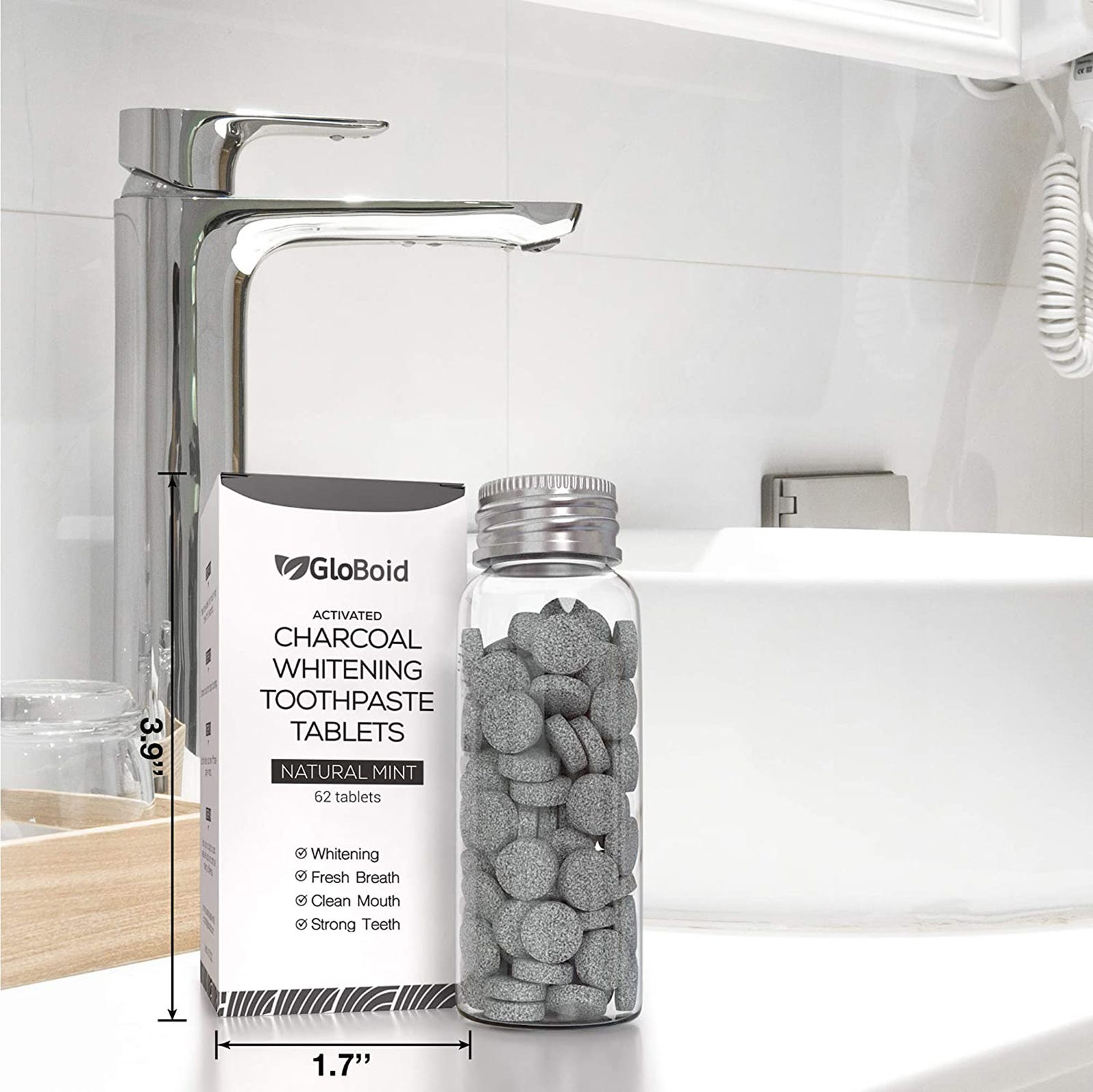 A see-through container with GloBoid's activated charcoal toothpaste tablets standing next to its box on a sink