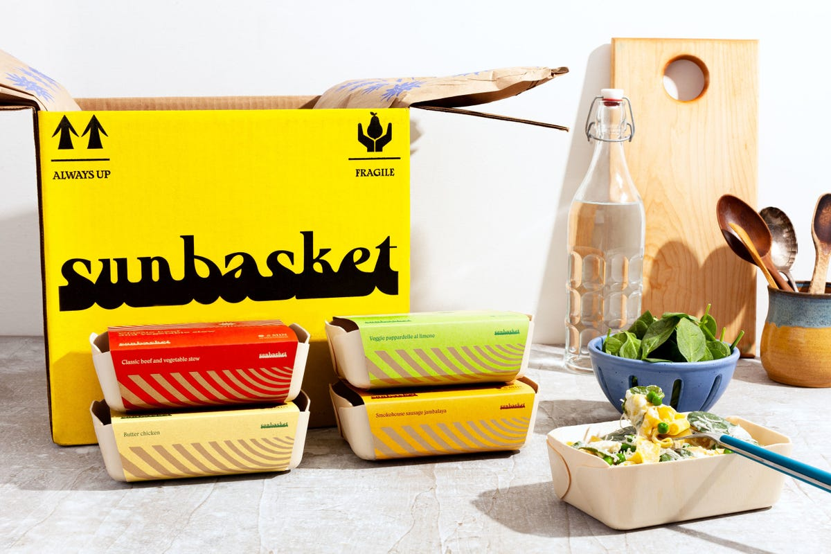 A cooked meal and four ready-to-eat meal boxes stacked on top of one another in front of a Sunbasket box.