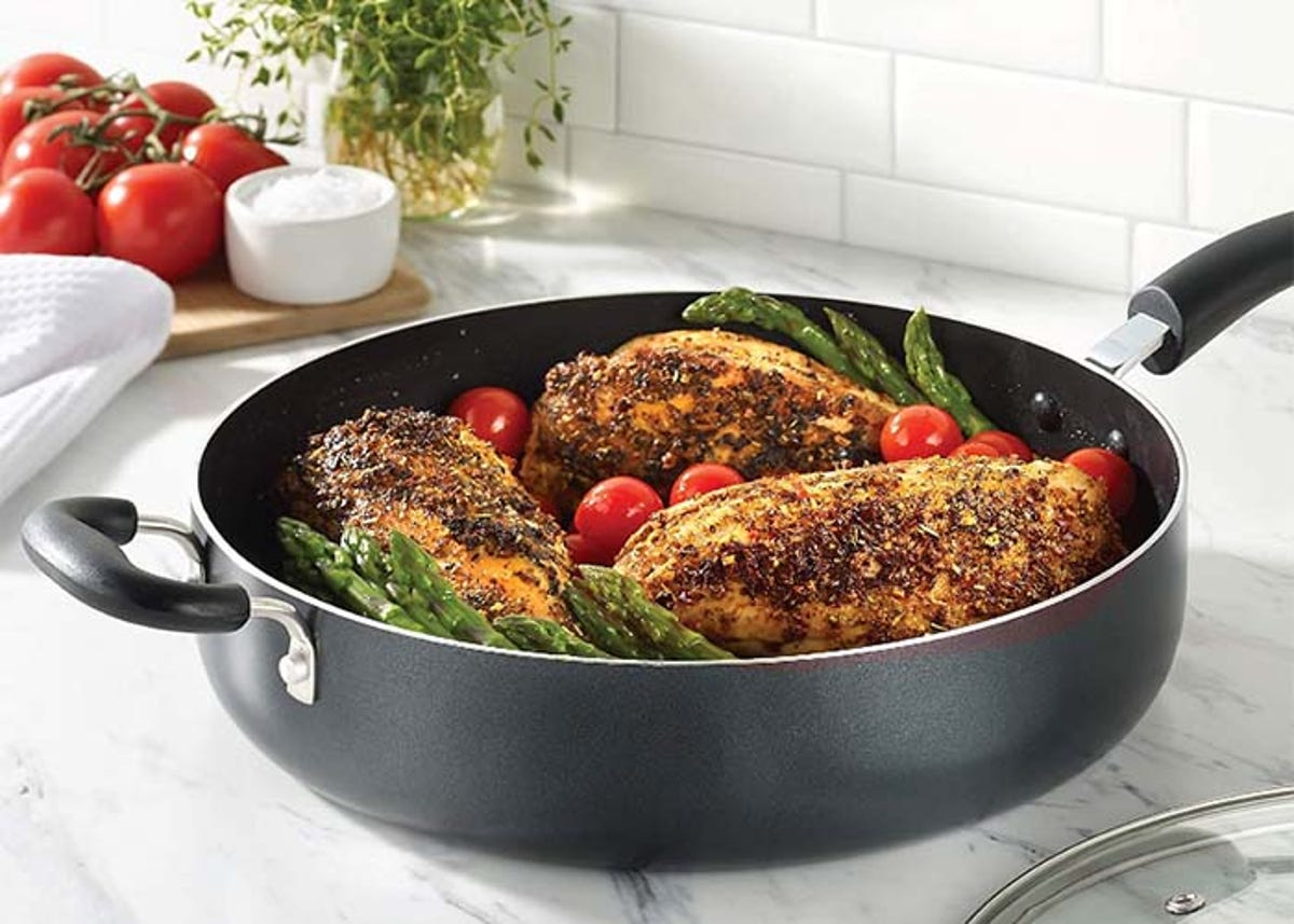 sauté pan holding chicken, asparagus, and tomatoes