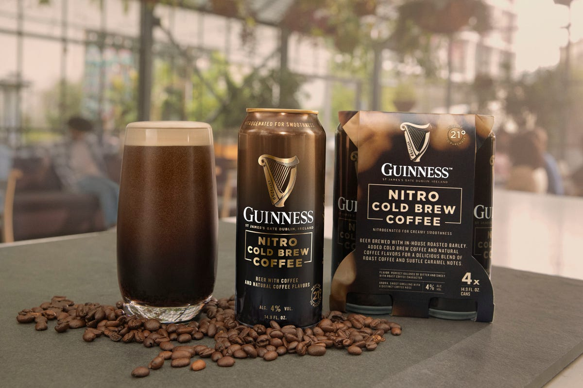 A Guinness Nitro Cold Brew Coffee can sits between a four-pack and a pint in a glass.
