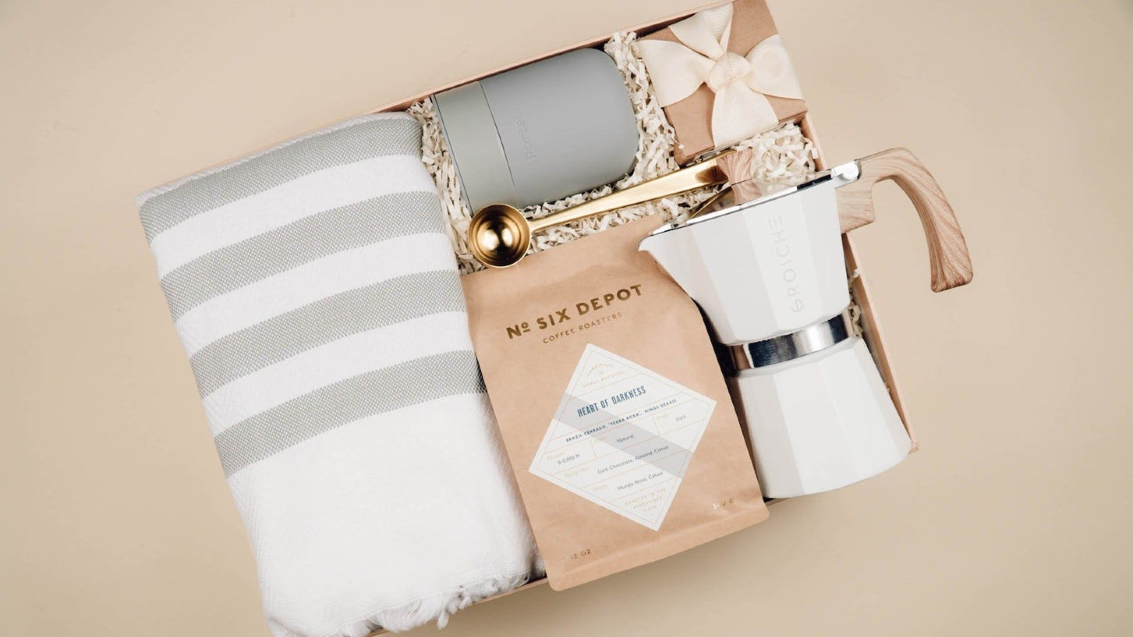 a gift box with a striped blanket, a white espresso maker, a gray mug, a small gift box, a coffee scoop, and a bag of coffee