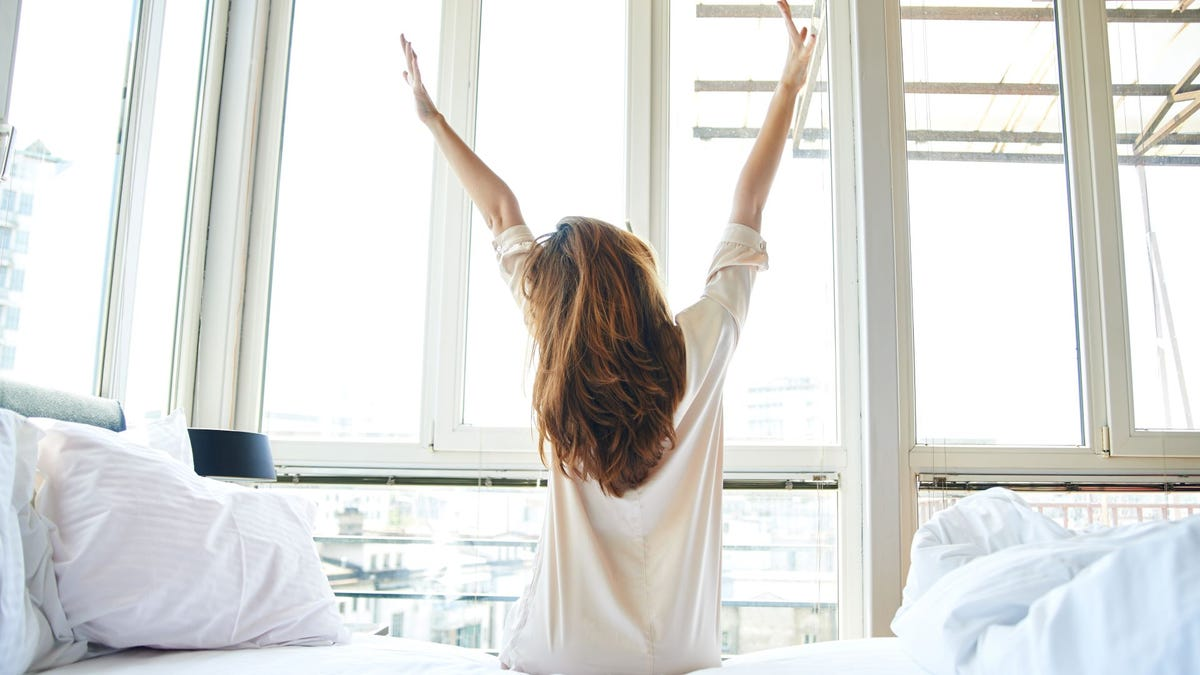 A woman waking up in the morning and stretching her arms overhead.