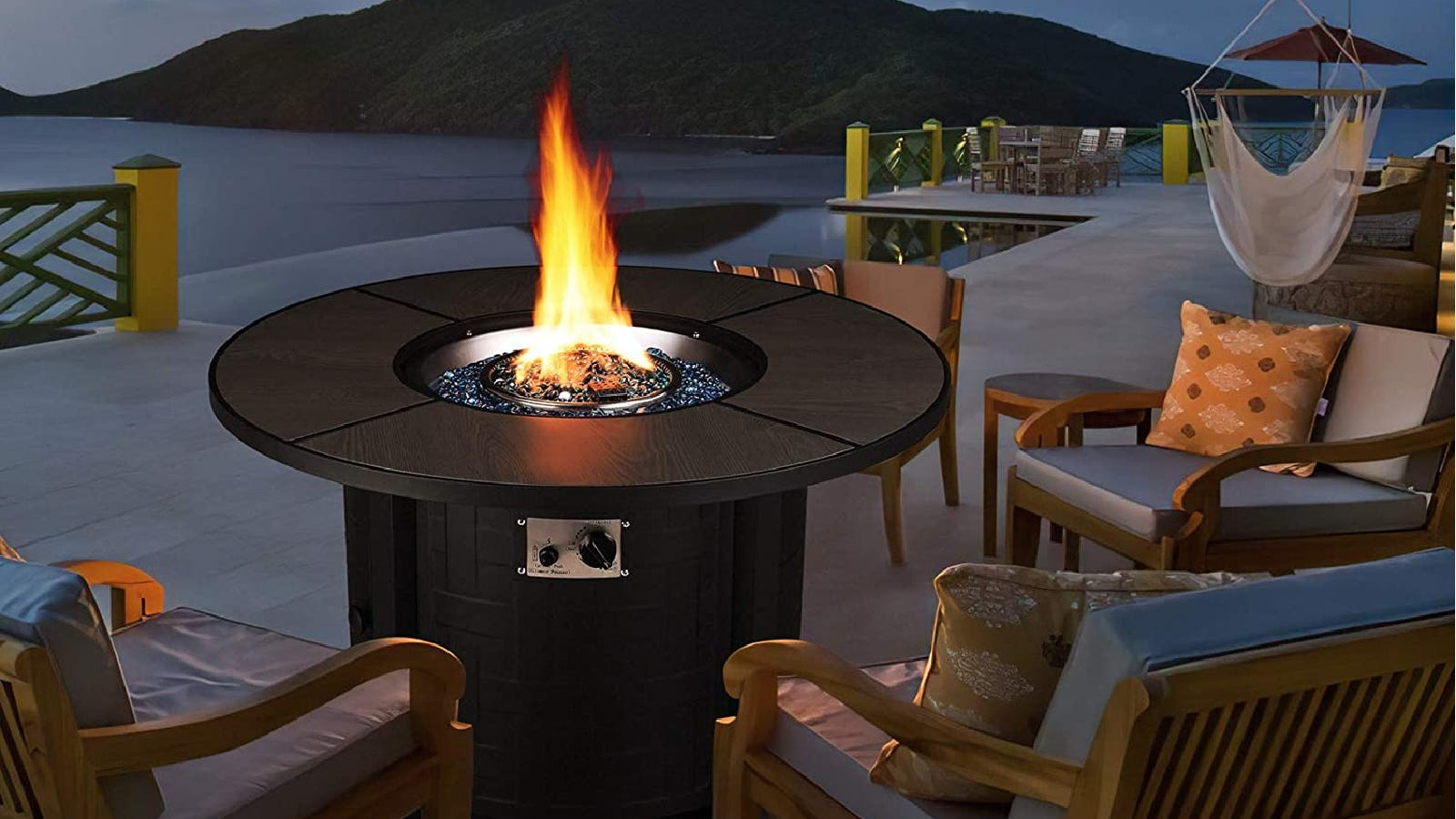 A round fire pit table, with an ignited flame on a warm evening with the moon shining ever so slightly over a gorgeous outdoor setting, surrounded by patio chairs.
