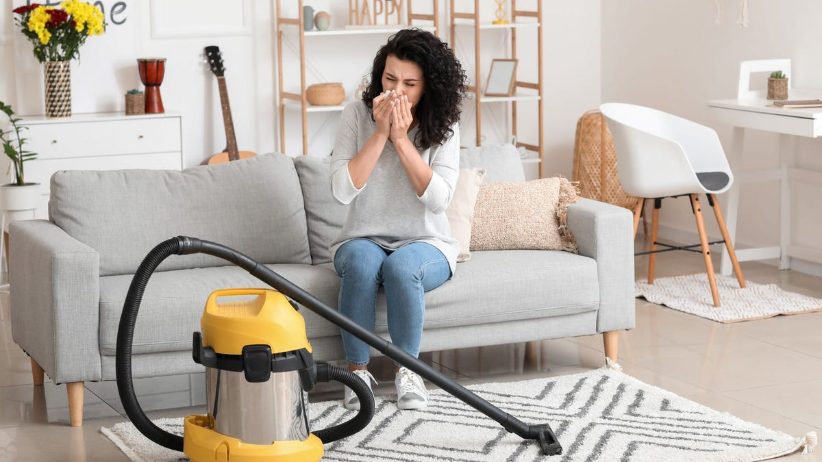 A woman suffering from allergies while vacuuming.