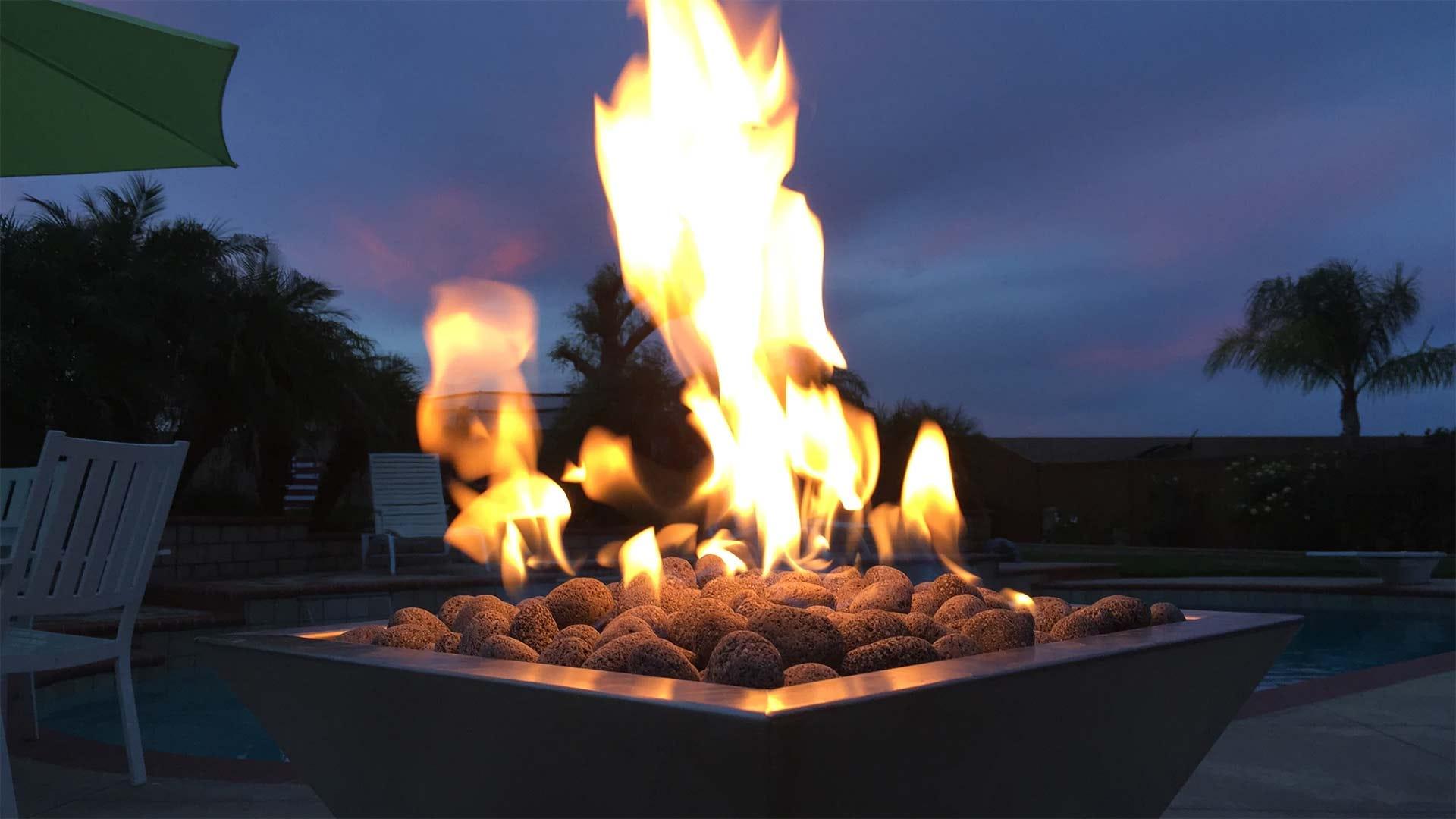 Uma mesa de fogo do quintal carregada com pedras de lava.