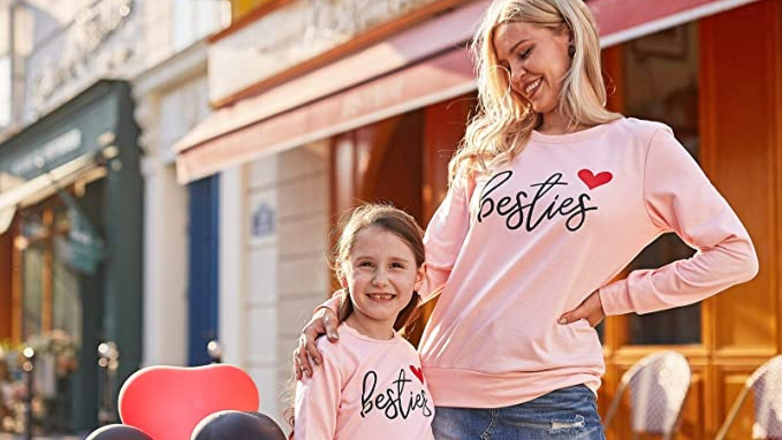 "blonde mother and daughter smiling and wearing matching pink sweatshirts that say ""besties"" with a heart"