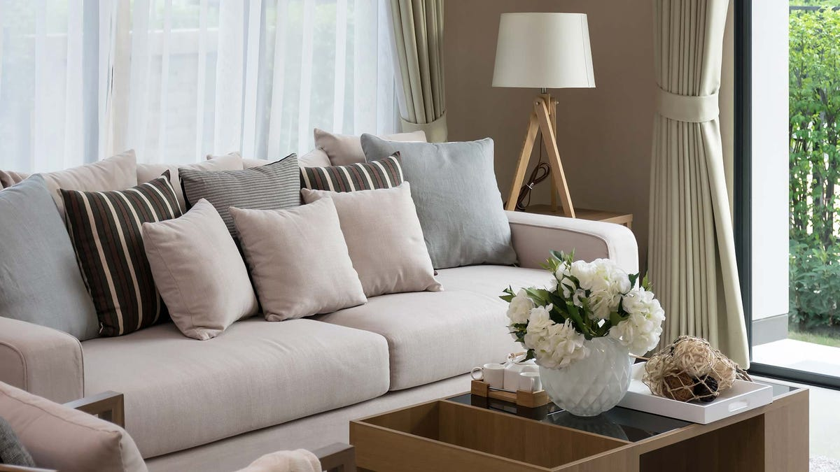 A contemporary living room with a couch covered in pillows.