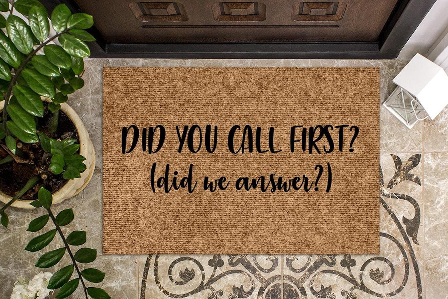 """A doormat reading """"Did You Call First? (Did We Answer?)"""""""