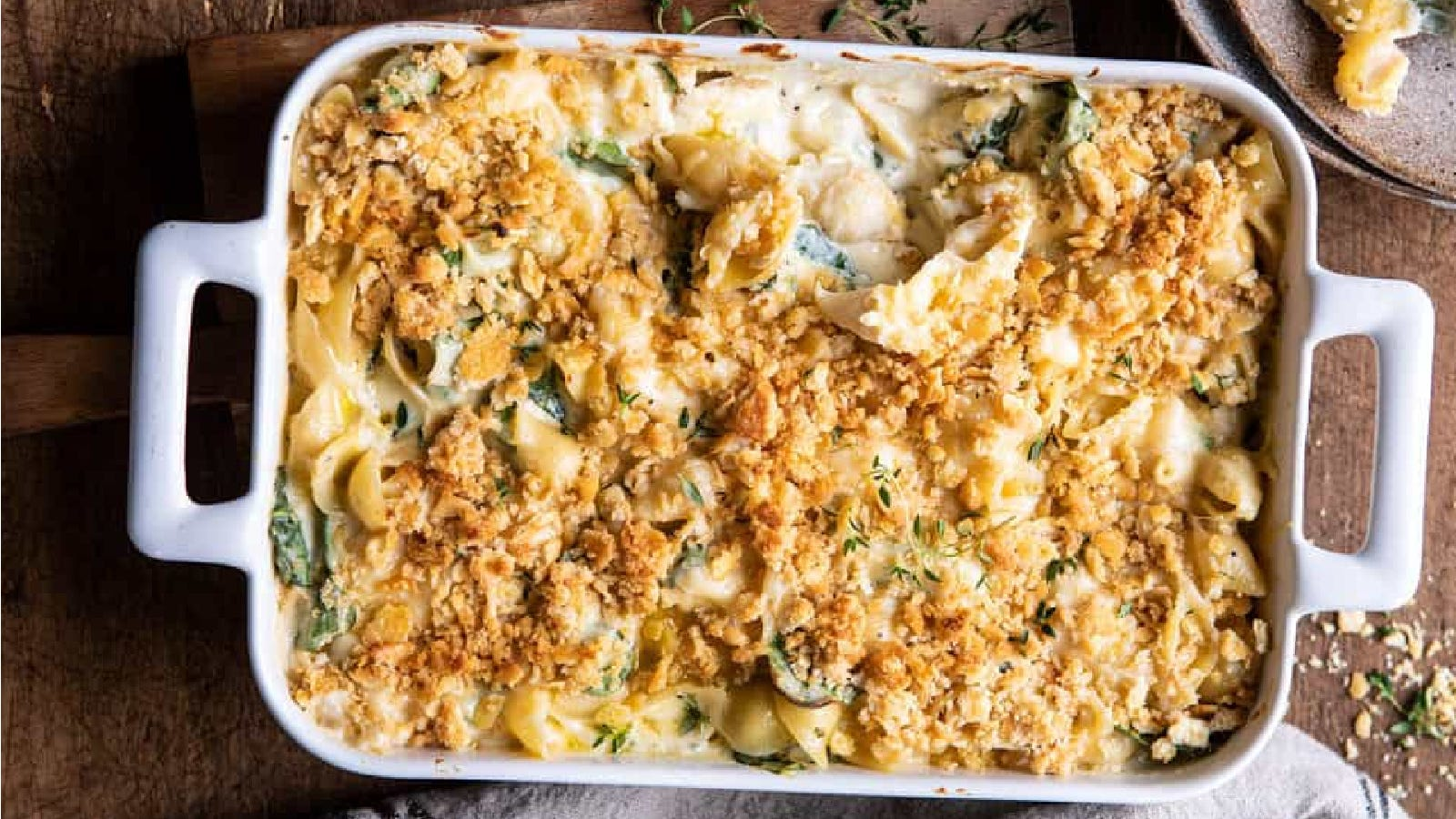 A casserole dish, filled with cheesy spinach and artichoke macaroni and cheese.